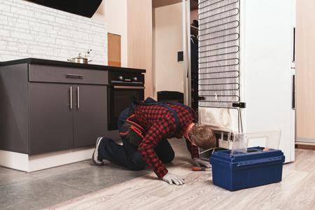 Ups, Sie haben ein Problem. Junger männlicher Techniker überprüft Kühlschrank