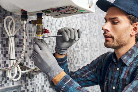 Schraubenschlüssel immer dabei. Arbeiter richten elektrischen Heizkessel zu Hause Badezimmer