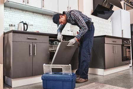 Servicio a tiempo. Técnico masculino sentado cerca de lavavajillas