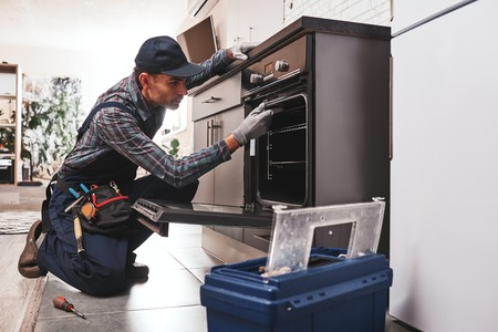 Dont delay with repair. Close-up of repairman examining oven 写真素材