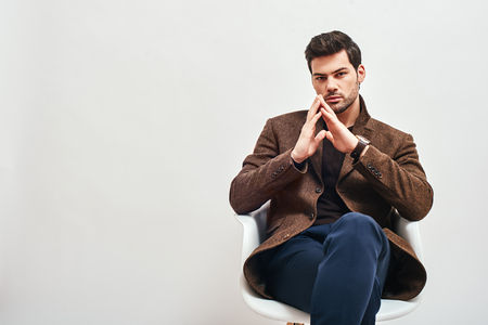 Waiting for interview. Stylish dark-haired man sitting on a chair, crossing his legs and looking at camera isolated over white background