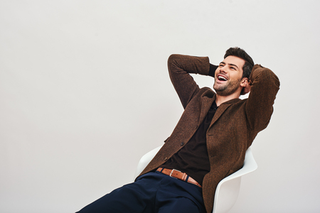 A good laugh heals a lot of hurts. Stylish dark-haired businessman sitting on a chair, leaning back and laughing isolated over white background