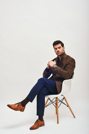 Stylish dark-haired man sitting on a chair and looking at camera isolated over white background