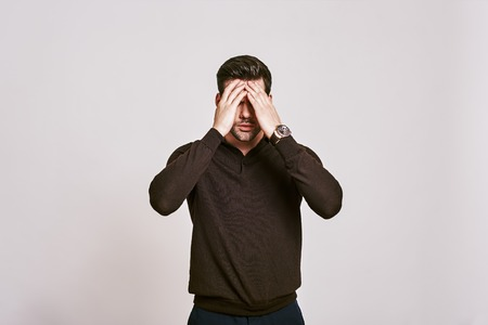 Emotional stress. Dark-haired man touching his head with hand feeling strong headache, standing isolated over white background.