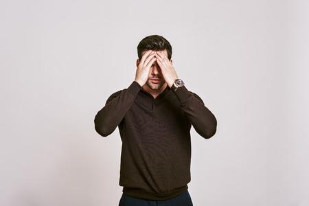 Estrés emocional. Hombre de cabello oscuro tocando su cabeza con la mano sintiendo un fuerte dolor de cabeza, que se encuentran aisladas sobre fondo blanco.