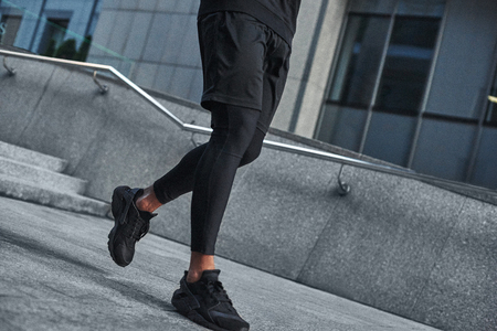 Starting to run. Cut view of male muscular feet in black sportswear and sneakers running against modern city. Cardio training