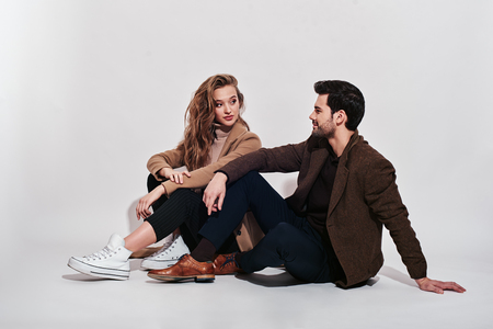 Always in style. Attractive and well-dressed couple posing in studio. They are looking at each other, while sitting on the floor. Isolated over grey background