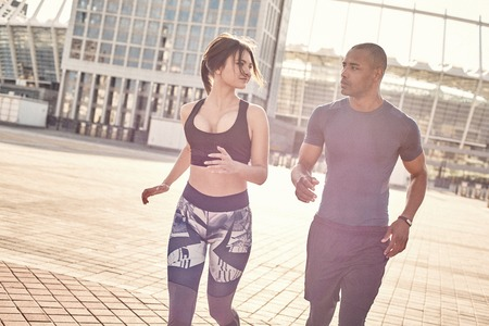 Keeping fit. Cute young interracial couple are doing morning workout and jogging together. Common hobbies