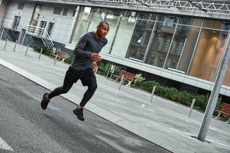 Confident runner. Full length portrait of athletic african man in sportswear running with very fast speed through the city streets Stock fotó - 117239947