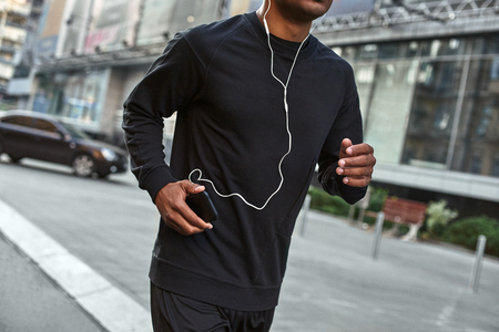 Great song for exercising. Close-up portrait of athletic african man in stylish sportswear running outside and listening to music on his smartphone