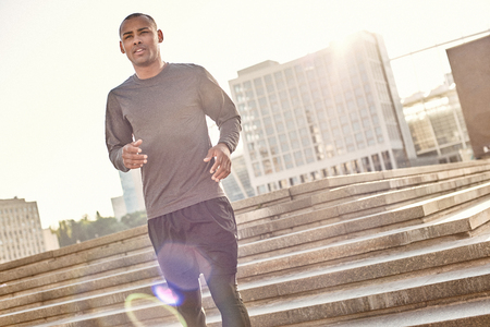 What a great day for workout! Full length portrait of athletic african man in sportswear jogging down stairs