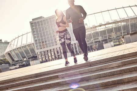 Enjoying workout together. Full length portrait of sporty and young interracial couple in sportswear running down the stairs in the urban environment. Common hobbies Stock Photo