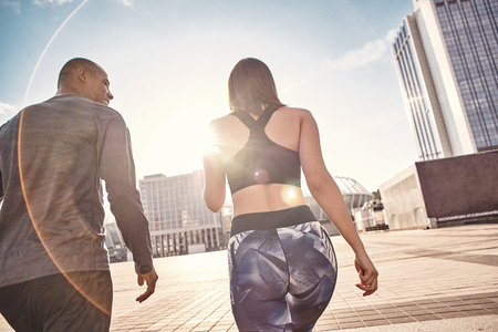 That was great workout! Back view of young multiracial couple in fitness clothes going home after morning training together. Common hobbies