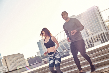 Jogging together. Athletic young interracial couple are running down the stairs together while morning workout. Common hobbies