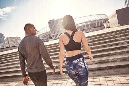 After great workout. Back view of young multiracial couple in fitness clothes going home after active training together. Urban environment Stock Photo