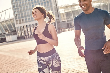 Perfect training. Positive mixed race couple: sporty african man and brunette girl in sportswear running together on a sunny warm day.
