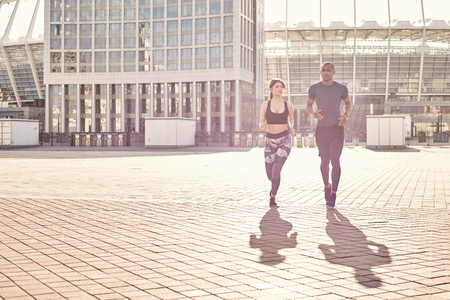 Positive and sporty mixed race couple: handsome african man and brunette girl in sportswear running together on a sunny warm day.