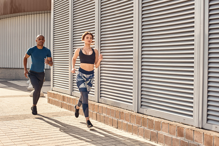 I am winning! Fitness couple in sports clothing doing cardio training in the city