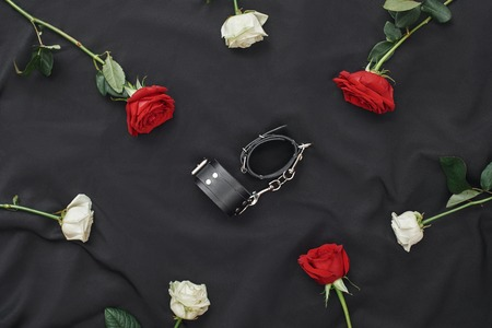 Composition of red and white roses with black leather handcuffs against of black silk fabric