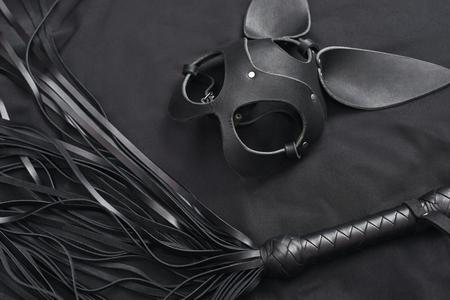 Draufsicht des Lederkits (schwarze Peitsche und Maske) gegen eine schwarze Seide. Standard-Bild
