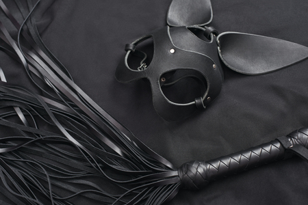 Impress him. Top view of bdsm leather kit (black whip and mask) against of a black silk. Stock Photo