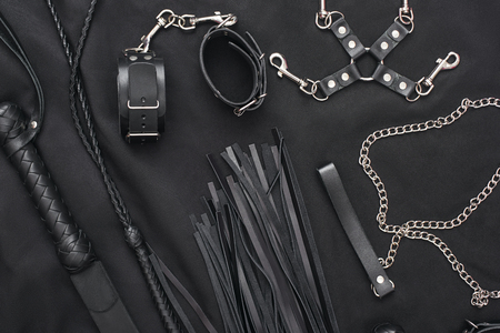 Top view of bdsm leather kit (whips, handcuffs, mask and chain) against of a black silk. Foto de archivo