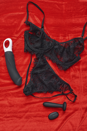 Made specially for women. Top view of black sexy lingerie and sex toys on red velour fabric. Stockfoto