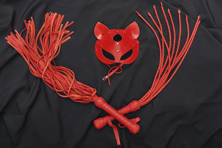New to BDSM? Top view of red bdsm leather set (whip and mask) on a black silk.