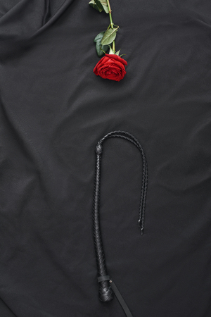 Enter the world of BDSM. Top view of black leather whip and red rose against of black silk