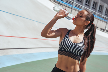 Stay hydrated. Runner on the stadium track. Woman summer fitness workout. Jogging, sport, healthy active lifestyle concept