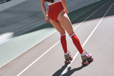 Close up of girls legs in the skatepark. She is rollerblading. Back view