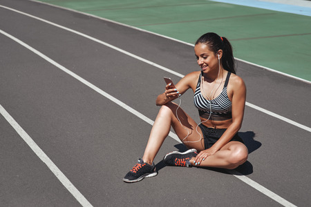 Stay tuned. Runner is sitting on the stadium track. Woman summer fitness workout. Jogging, sport, healthy active lifestyle concept