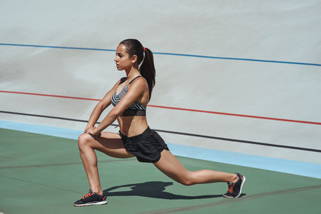 More stretching, less stressing. Attractive athlete on the stadium track. Woman summer fitness workout. Jogging, sport, healthy active lifestyle concept