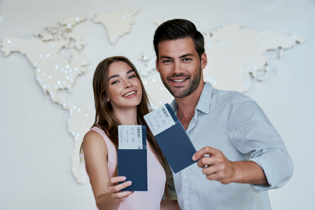 Portrait of joyful glad couple holding passport with flying tickets in hands 写真素材