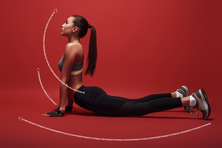 Sport is the way of her life. Sportswoman lying over red background, stretching her body. Graphic drawing. Standard-Bild - 119687284
