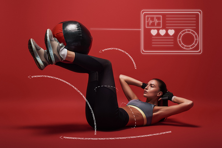 Best exercise. Sportswoman lying over red background, working her abs