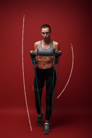 Born to win. Beautiful sportswoman performs exercises with resistance band over red background. Graphic drawing. Stock Photo