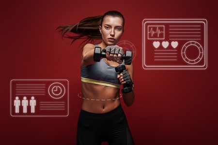 Never stop Sportswoman is exercising with dumbbells standing over red background. Game concept. Stock Photo