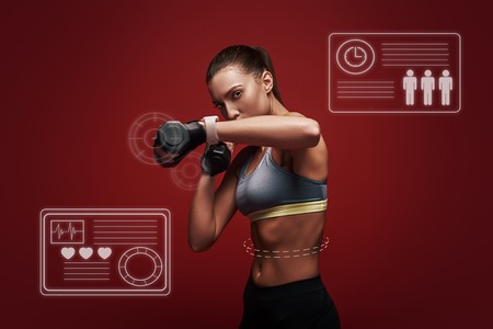 Train insane or remain the same. Sportswoman is training with dumbbells standing over red background. Game concept. Stock Photo