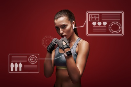 Modern athlete. Sportswoman standing concentrated in gym gloves over red background. Game concept with graphic drawing.