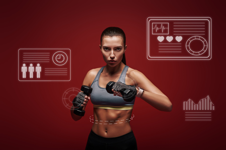 Strong and confident. Sportswoman holds dumbbells standing over red background. Game concept. Stock Photo
