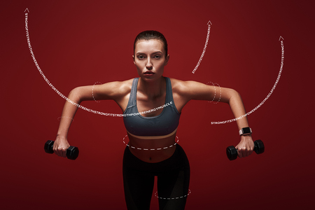 Everyday is a choice. Sportswoman holds dumbbells standing over red background. Graphic drawing. Reklamní fotografie