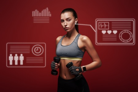 Dedicated to fitness. Sportswoman holds dumbbells standing over red background. Game concept. 写真素材