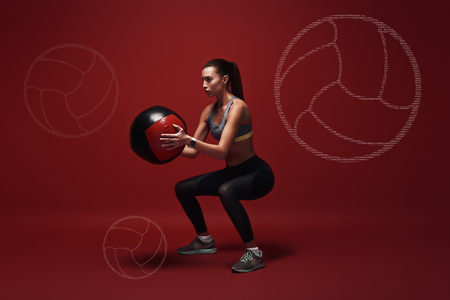 Awesome exercise. Sportswoman holds exercise ball standing over red background. Graphic drawing.