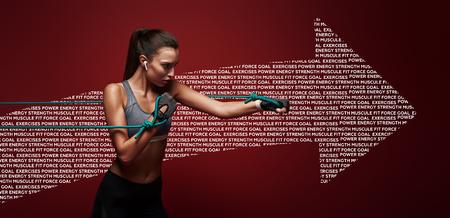 Usalo o perdilo. Sportiva esegue esercizi con banda di resistenza su sfondo rosso. Disegno grafico. Archivio Fotografico