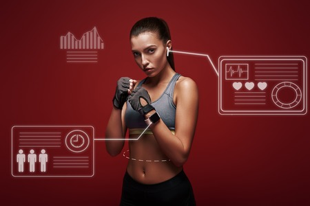 New champion. Young sportswoman standing over red background is ready to exercise. Game concept with graphic drawing.