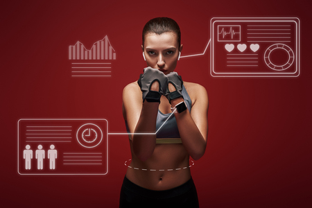 Strong fighter. Young sportswoman standing over red background is ready to exercise. Game concept with graphic drawing.