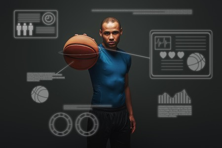 Keep it up. Handsome sportsman standing over dark background with basketball ball in his hand. Game concept with graphic drawing.