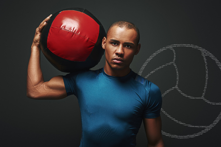Serious about staying in a good shape. Close up of sportsman standing with a ball over dark background. Game concept with graphic drawing.