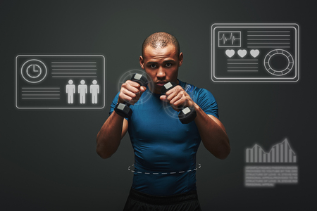 Ready to fight Handsome young sportsman working out with dumbbells over dark background. Game concept with graphic drawing. Stock Photo